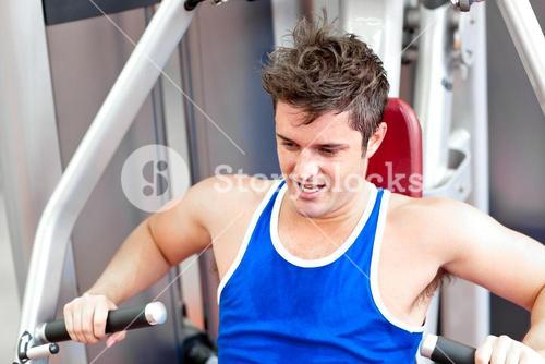 Athletic young man using a bench press