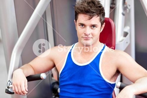 Selfassured young man using a bench press