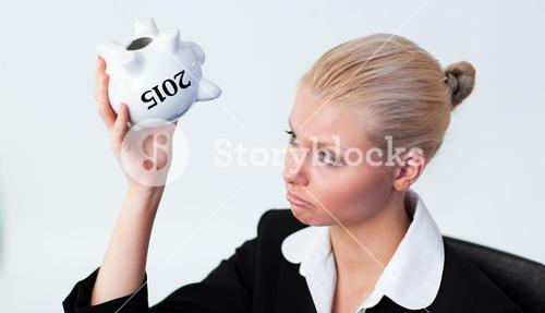 Composite image of sad business woman looking into piggy bank