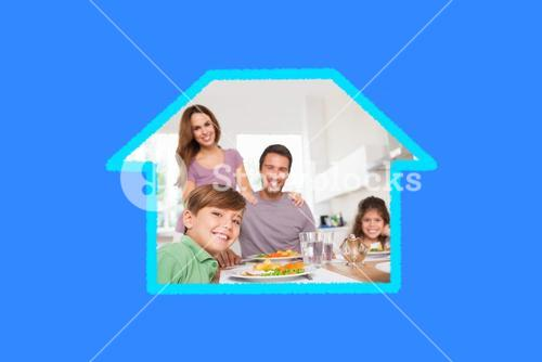Composite image of family looking at the camera at dinner time