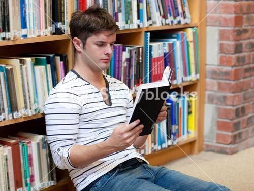 Handsome young man reading a book sitting on the floor