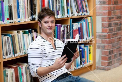 Handsome male student reading a book sitting on the floor