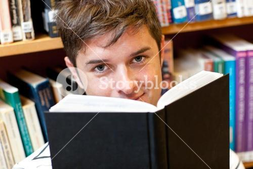 Portrait of a goodlooking male student reading a book sitting on the floor