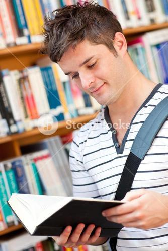 Cute male student reading a book