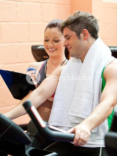 Handsome male athlete exercising on a bicycle with his personal coach