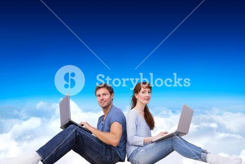 Composite image of couple both using laptops separately