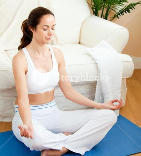 Concentrated woman doing yoga sitting in her livingroom