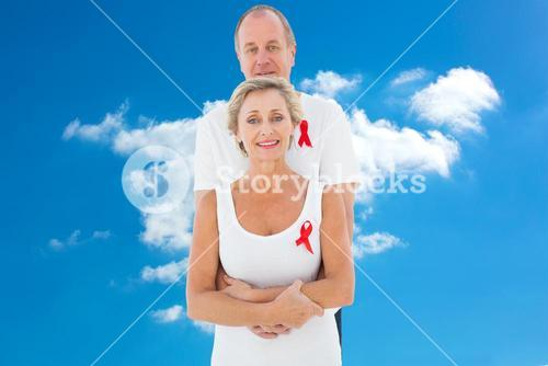 Composite image of mature couple supporting aids awareness together