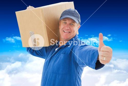 Composite image of happy delivery man holding cardboard box