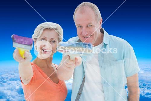 Composite image of happy older couple holding paintbrushes
