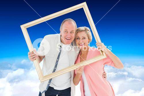 Composite image of older couple smiling at camera through picture frame