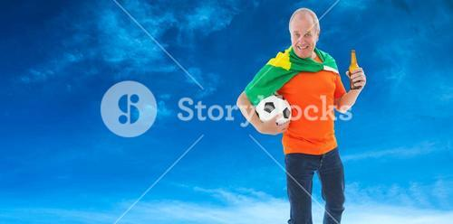 Composite image of mature man in orange tshirt holding football and beer