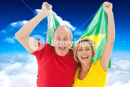 Composite image of happy older couple cheering at camera holding brazil flag