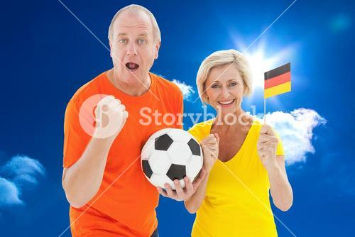 Composite image of happy german couple cheering at camera holding ball