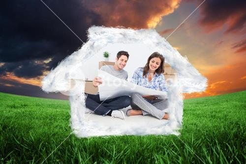 Composite image of man and woman looking at their house plans