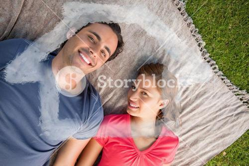 Composite image of two friends looking towards the sky while lying on a quilt