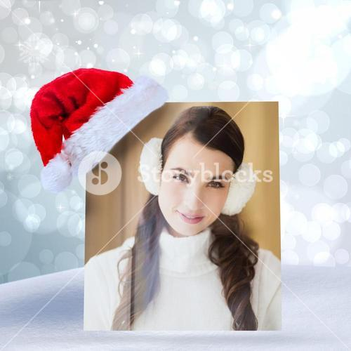 Composite image of pretty brunette with ear muffs smiling at camera