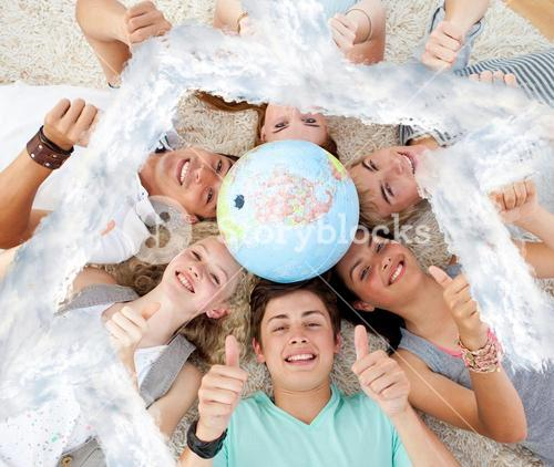 Composite image of teenagers on the floor with a terrestrial globe in the center and with thumbs up
