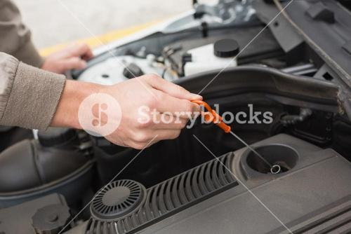 Man using dipstick to check oil