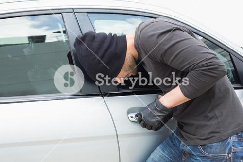 Thief breaking into a car