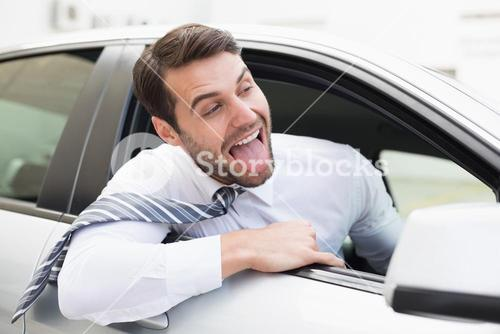 Carefree businessman sitting in drivers seat