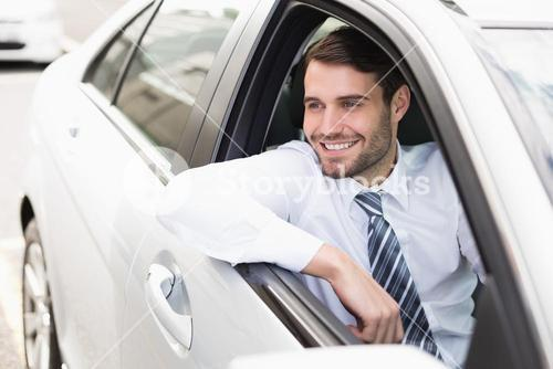 Happy businessman sitting in drivers seat