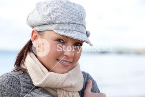 Portrait of a delighted young woman with cap and scarf standing on the beach