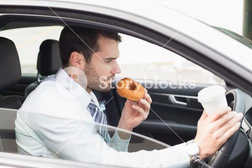 Young businessman having coffee and doughnut