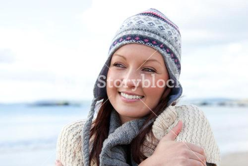 Frozen woman with scarf and colorful hat standing on the beach