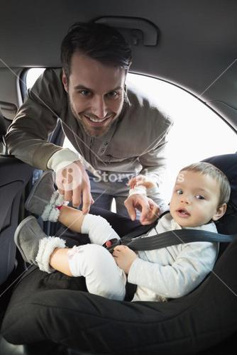 Father securing his baby in the car seat