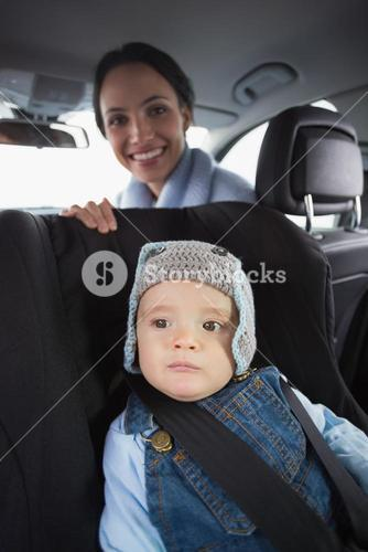 Mother checking her baby in the car seat