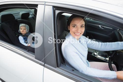 Mother driving with her baby in the car seat