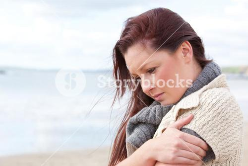 Worried woman wearing sweater on the beach and getting cold