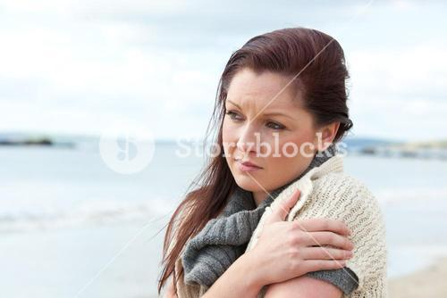 Unhappy woman wearing sweater on the beach and getting cold