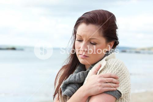 Worried woman wearing hat and scarf on the beach