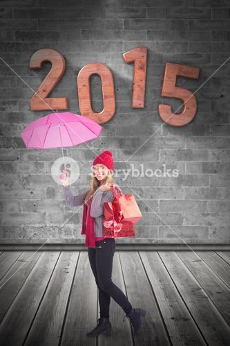 Composite image of festive blonde holding umbrella and bags