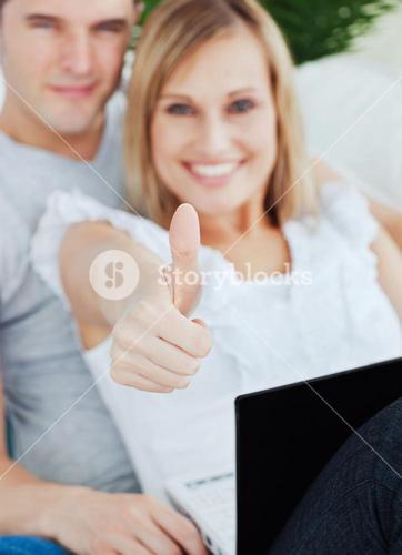Young couple working on a laptop with girlfriend doing a thumbsup