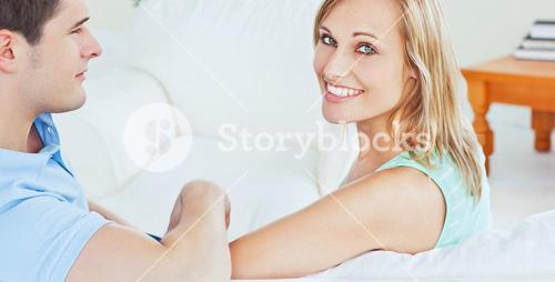 Smiling young couple sitting on a sofa
