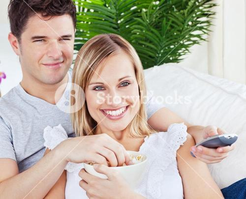 Young couple having fun in front of the TV