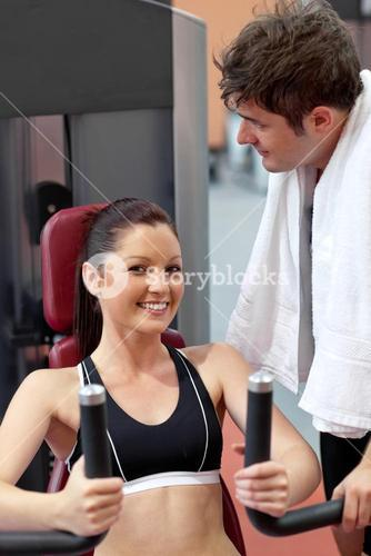 Smiling woman sitting on a bench press with her boyfriend standing next to her