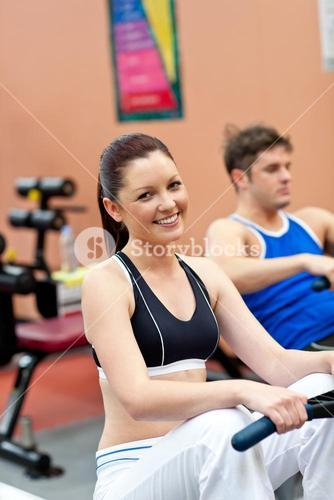 Beautiful woman using a rower with her boyfriend in a fitness center