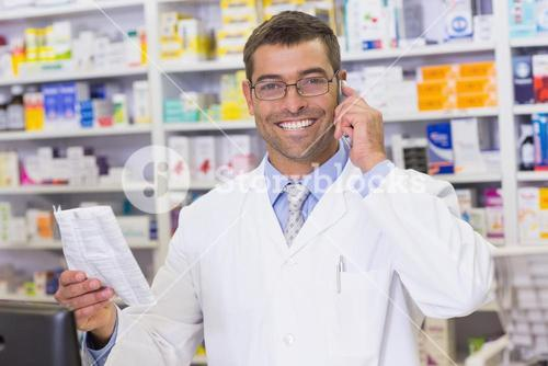 Happy pharmacist on the phone looking at the camera