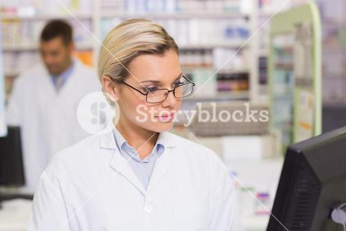 Concentrate pharmacist looking at computer