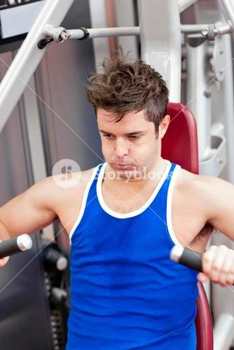 Young man putting a lot of effort sitting on a bench press