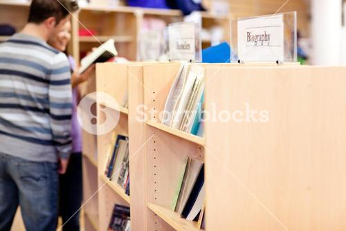 Close up of a bookshelves in a library with students reading book