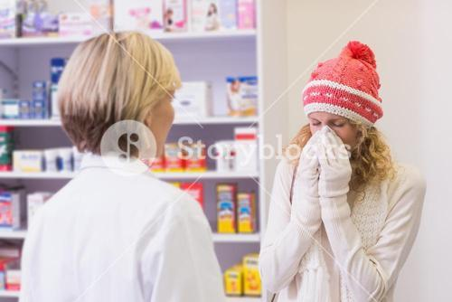 Costumer blowing in front of pharmacist