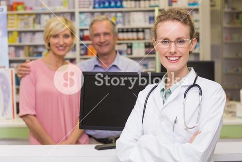 Pharmacist and costumers smiling at camera