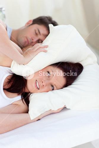 Stressed future mom with head under the pillow in bed with her husband snoring