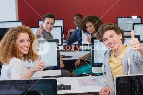 Students smiling at camera in computer class