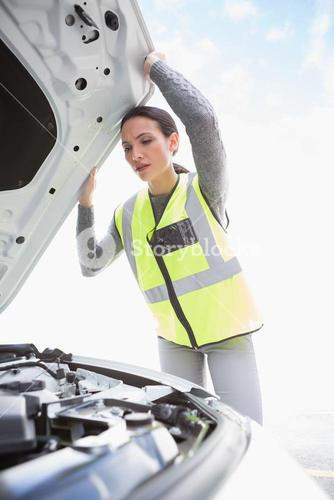 Upset woman checking her car engine